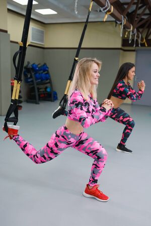 Happy Women perform exercises with suspension straps, fitness workout at gym, selective focus.
