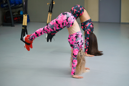 Two girls at gym perform exercises with suspension straps standing on hands upside down, fitness workout, selective focus.