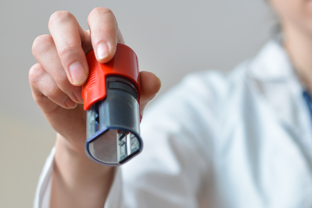 Female doctor holding rubber stamps in hand preparing to seal, closeup shoot. Stock Photo