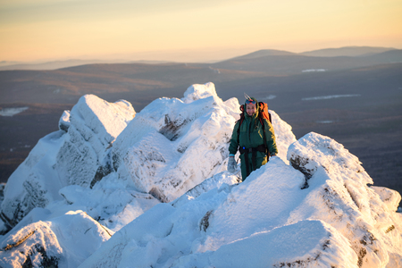 Happy Woman hiker with backpack standing on the mountain peak abd smiling at cold winter day. Female hero and active lifestyle concept. Stock Photo