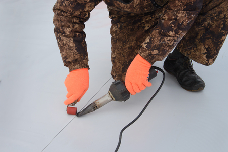 Waterproofing and insulation at construction site, roof sealing process of synthetic membrane with Hot Air Hand Tool. New protection technology. Closeup.