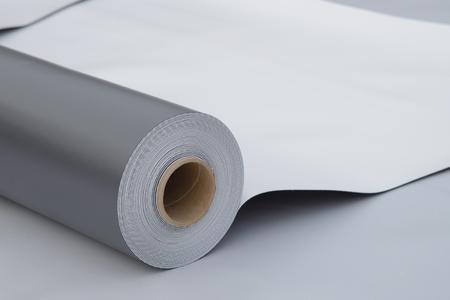 Imprägnierung und Isolierung an der Baustelle, geöffnete PVC-Membranrolle, die auf Dachnahaufnahme liegt. Kopieren Sie Platz für Ihren Text.