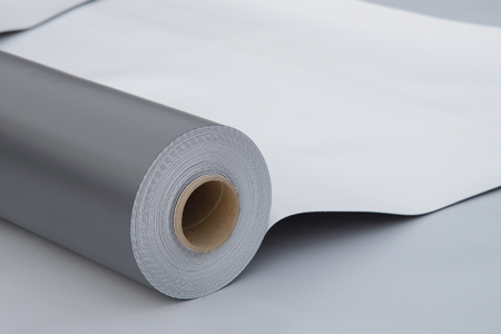 Waterproofing and insulation at construction site, opened pvc membrane roll lying on roof closeup. Copy space for your text. Standard-Bild