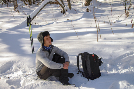 Young Man hiker in snowy forest take a rest during trekking. Winter leisure, sports and activity. Stock Photo