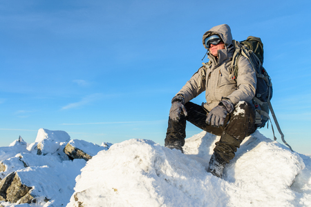 Hiker with backpack sitting and having rest on the top of a snow-covered rock over the winter mountains
