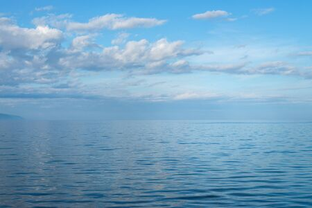 Clear crystal water of Lake Baikal in calm weather . Blue sky and clouds reflection. Stock Photo
