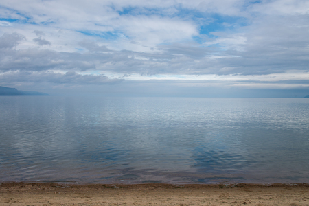 Clear crystal water of Lake Baikal in calm weather . Blue sky and clouds reflection