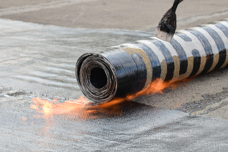 Roofing installation felt with heating and melting bitumen roll by torch on flame, closeup detail shoot Stock Photo