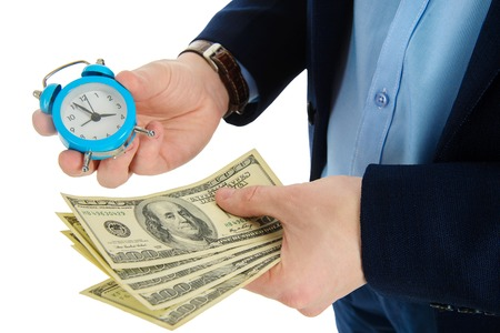 Close up of businessman holding a clock and one stack of cash in hand, time and money concept. Making right decision.