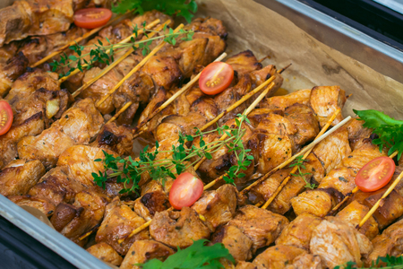 Fresh grilled pork shish kebab served with tomato cherry and greens on skewers on hot plate, closeup