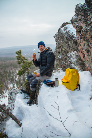 Man hiker have a rest at mountain top, drinking tea and eating during winter adventure.