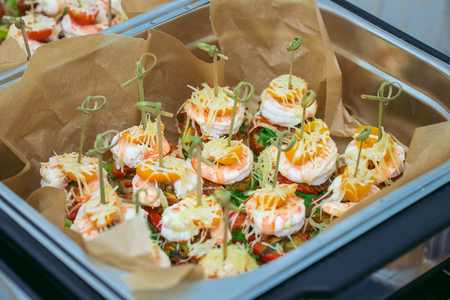 Hot Delicates, appetizer canape with tiger shrimp, fused cheese and vegetables. Catering service.