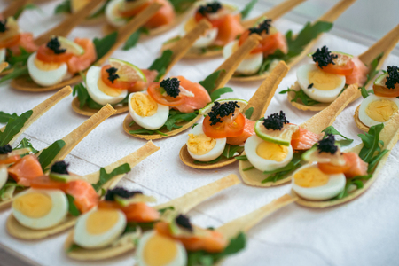 Delicates, appetizer filling with red fish, quail egg, black caviar and lime. Catering service.