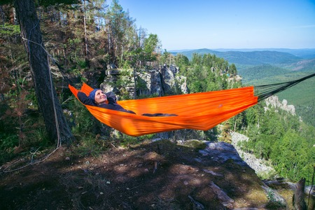 Happy woman relaxing lying in hammock on top of mountain. Summer travel lifestyle.