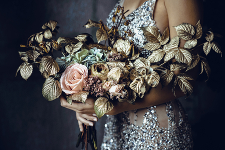Woman in silver dress holds a beautiful decorated bouquet of flowers and greenery on grey background, closeup shoot. Unrecognizable person. Banco de Imagens