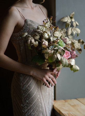 Woman hands holding beautiful decorated bouquet of flowers , closeup shoot.