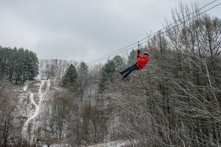 Russia, Izhevsk - November 18, 2018: Zipline. Man gliding on rope trolley over ravine on high altitude. Extreme and active leisure.