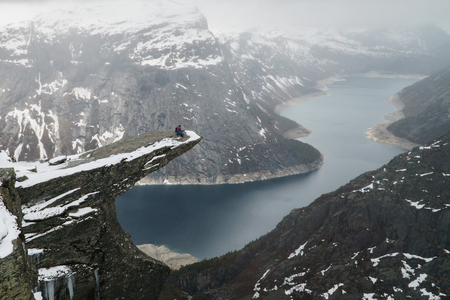 Trolltunga cliff under snow in Norway. Scenic Landscape. Man traveller sitting on edge of rock in yoga meditation pose. Travel, extreme and active lifestyle. Banco de Imagens