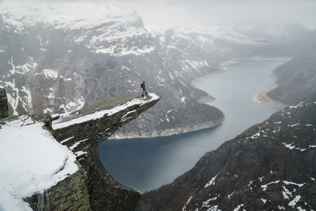 Trolltunga cliff under snow in Norway. Scenic Landscape. Man traveller standing on edge of rock and looking down. Travel, extreme and active lifestyle. Banco de Imagens