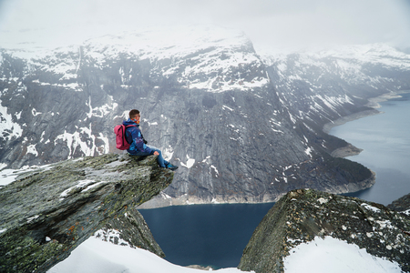 Trolltunga cliff under snow in Norway. Scenic Landscape. Man traveller sitting on edge of rock and looking at distance, scenic landscape. Travel, extreme and active lifestyle.
