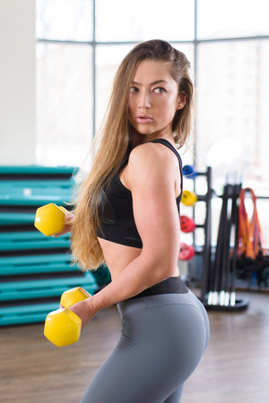 Young athletic woman training with dumbbells at gym. Fitness and healthy lifestyle concept. Beautiful caucasian girl posing during workout.