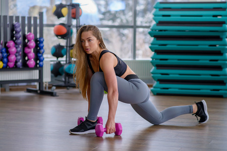Athletic young woman during workout at fitness class. Beautiful sexy girl with perfect body and shape posing with dumbbells at gym. Sport motivation.
