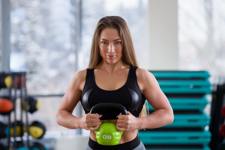 Athletic young woman during workout at fitness class. Beautiful sexy girl with perfect body and shape holding kettlebell at gym. Sport motivation.