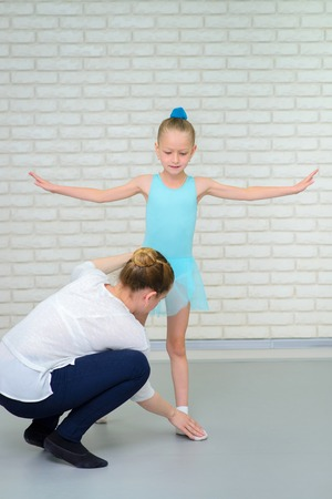 Education in ballet school. Teacher corrects pose of little ballerina in class. Cute little girl during dance practice.