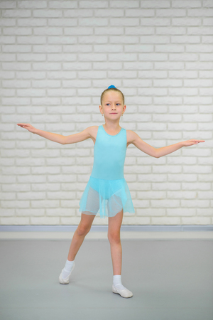 Little ballerina in blue dress and pointe shoes is dancing in ballet school. Cute girl in dance class. Banco de Imagens