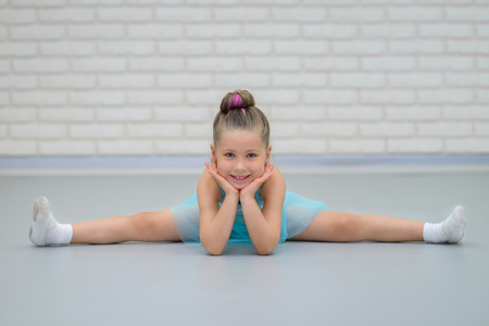 Cute little beautiful girl doing splits at ballet class. Young happy ballerina in blue dress stretching, smiling and looking at camera.