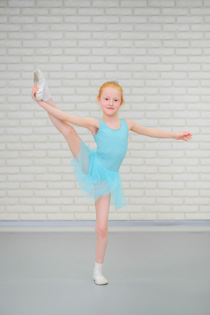 Cute little ballerina in blue dress dancing at ballet class.