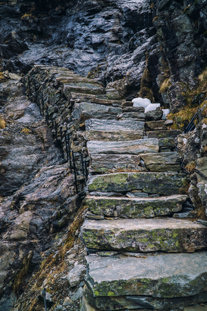 Ancient stone stairs going up on black rock, mountain stairway. Norway, Trolls road, Trollstigen. Banco de Imagens