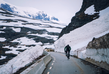 Cyclist on mountain road in Norway, cycling uphill on way after snow avalanche.