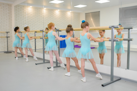 Little girls practicing ballet in studio near barre. Concentrating on exercise, view from back. 版權商用圖片