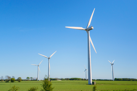 Windmills, Many wind turbines standing on field with lush green grass in spring, alternative energy sources.