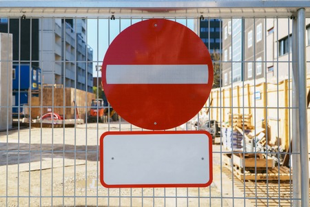 No entry sign on the fence in construction site of new apartment building in city, access is prohibited. Copy space for title.