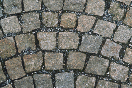 Old cobbled stone texture background, pavement structure on road.