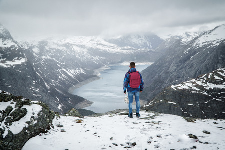 Man traveller with backpack standing back on edge and looking at scenery mountain landscape under snow, Trolltunga, Norway in may.