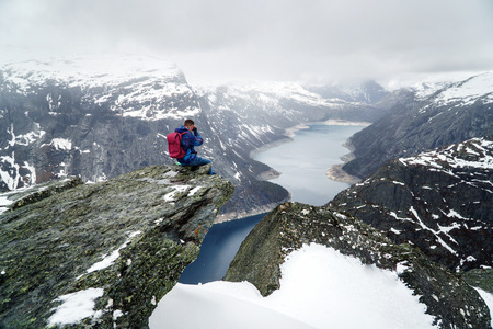 Trolltunga cliff under snow in Norway. Scenic Landscape. Man traveller sitting on edge of rock and making photos of scenic landscape. Travel, extreme and active lifestyle.