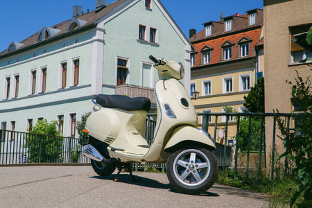 Vintage scooter on street of European city at bright sunny day, Regensburg, Germany.