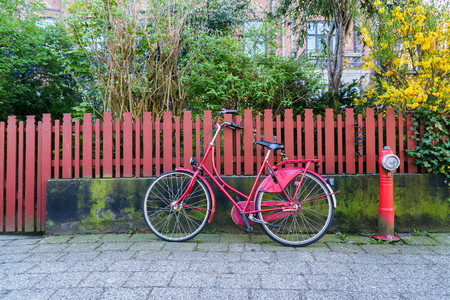 Nice Red vintage bike parked near wooden fence at city street.