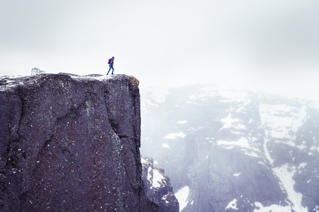 Lonely man on rock, traveller standing on high edge of cliff and looking at mountains in mist