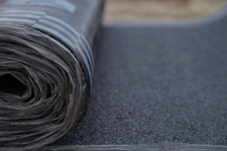 Waterproof bitumen roll covered with insulation materials, abstract background, closeup texture