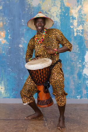 African man in traditional clothes playing djembe drum 写真素材