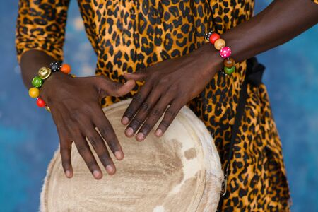 African male hands playing on jembe drum, closeup