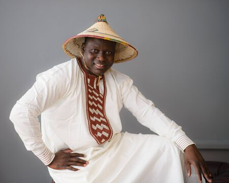 Handsome african man in traditional white dress and fulani hat on gray background 写真素材