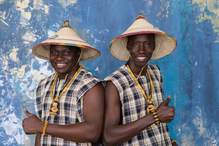 Two cheerful african men in traditional costumes showing thumbs up