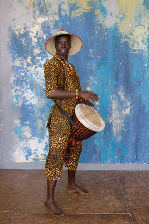 African man in traditional clothes playing djembe drum Stock Photo