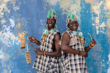 African artists with traditional musical instruments on blue wall background.