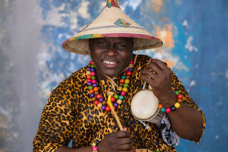 African man in traditional clothes and fulani hat playing on talking drum